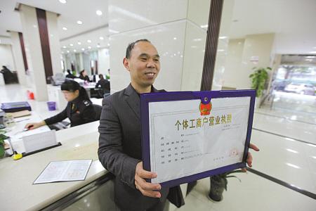"""刘先生领取首本""""多合一""""营业执照。(胡建华 摄)"""