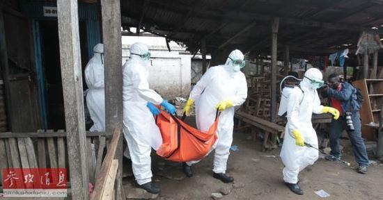 资料图片:在利比里亚首都蒙罗维亚,工作人员将感染埃博拉病毒死亡者的尸体带离居民区。新华社发(马库斯摄)