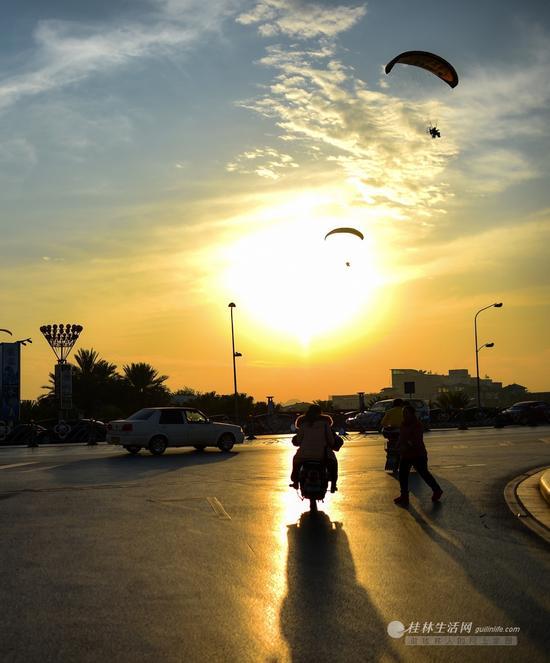 解放桥东,汽车、电动车、飞伞在夕阳下构成一幅美景。