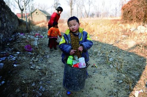 三个孩子在村子周边捡拾垃圾贴补家用