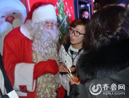 """一位热心的济南大妈,给芬兰圣诞老人送来了他很喜欢吃的""""甜不辣""""。"""