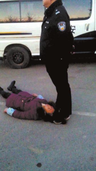 事发现场一名身穿警服的男子疑似用脚踩着女农民 工周秀云的头发