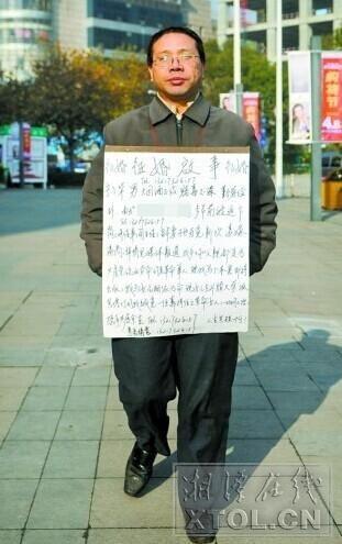 12月29日,岳塘区建设路口,宁小华将征婚启事挂在胸前。 (记者 张哲 摄)