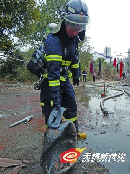消防员从失火房屋内取出已变形的液化气瓶。
