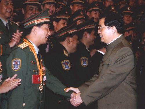 2005年6月22日,时任中共中央总书记、国家主席、中央军委主席胡锦涛与独臂英雄丁晓兵亲切握手。(资料图新华社)