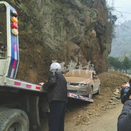 省道306线金口河段,被落石砸中的小车被拖走。