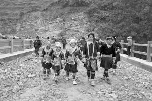 一群妇女和孩子穿着艳丽的民族服装,兴高采烈地从宁波桥上走过。 记者 范洪 摄