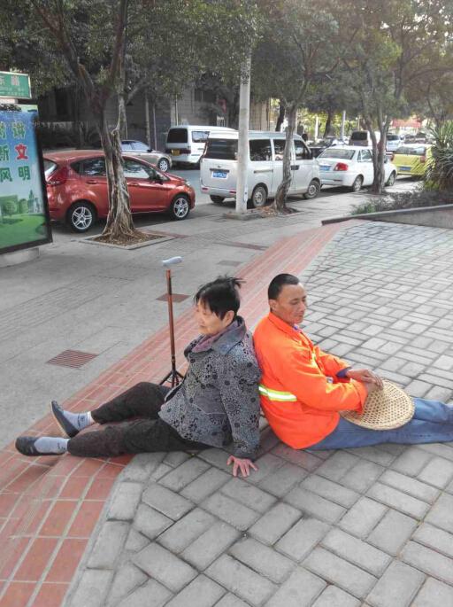 翁阿婆在自家楼下散步时突然双腿失去知觉瘫倒在路中间,附近清扫的环卫工人杨妹仔担心大冬天的老人躺在地上着凉,便坐在老人身后,用自己的背作支撑让老人依靠