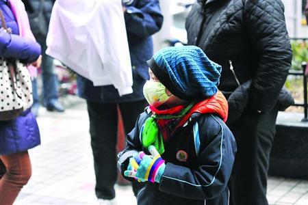 □昨日,为预防感冒,部分学生戴口罩上学。/晨报记者 陈征
