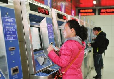 几位市民在自动售票机前自助买票取票