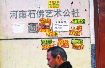 曾经的石佛艺术公社招牌已被搬家小广告﹃侵占﹄。