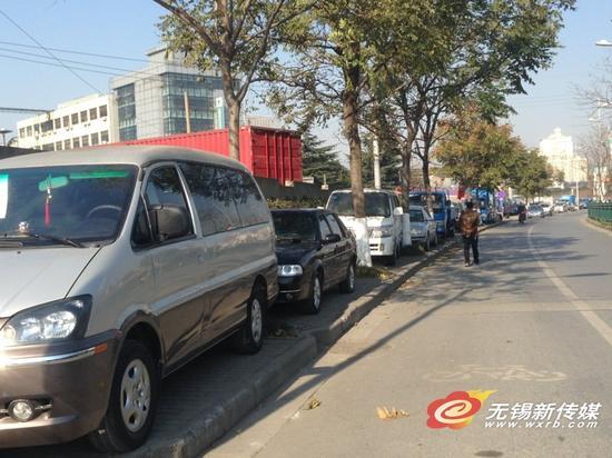 贡湖大道人行道板上停满了车,行人只好在非机动车车道上行走。