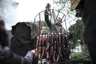 2014年12月30日8时许,重庆巴南区毛纺厂,居民将风干的香肠挂上熏架。每年这时候,居民们就会熏制香肠、腊肉、排骨等过年食物。