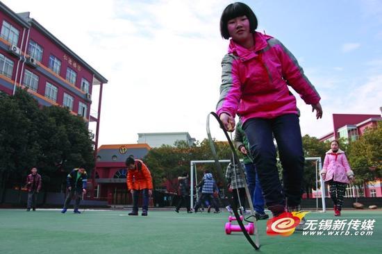 扬名中心小学学生在玩滚铁环