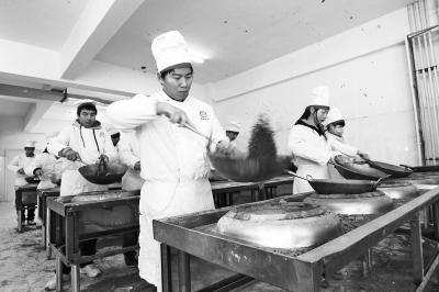在长垣烹饪职业技术学院,学员们用沙土练炒菜。
