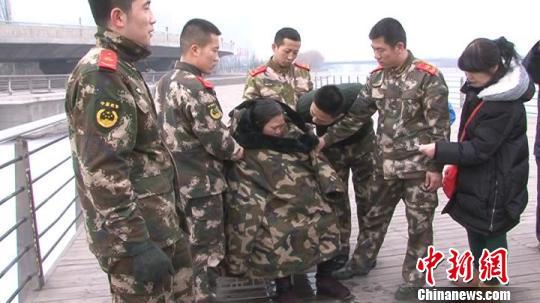2日中午,太原一名女子不慎落水,10名消防官员将其救上岸后,纷纷脱下衣服为女子取暖。屈丽霞摄