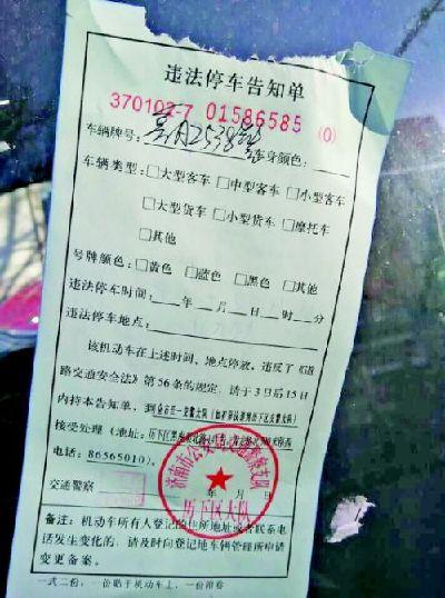 5日下午,一辆停在路东侧车道的警车被贴罚单。本报记者王皇实习生卢燕摄