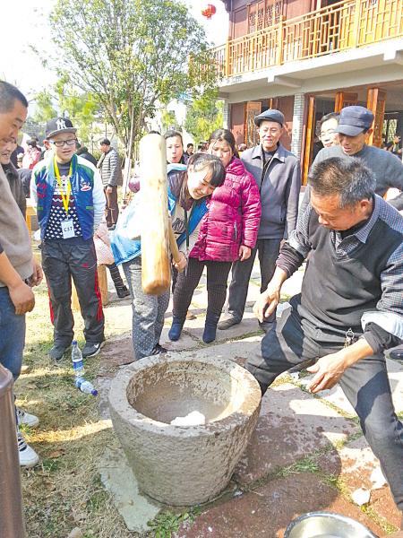 图为游客在毛岙村广场参与制作年糕。(曹爱方 摄)