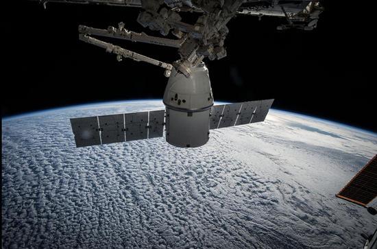 """在机械臂的协助下即将与空间站分离的SpaceX公司""""龙""""飞船。"""