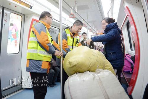 地铁工作人员帮忙把乘客的行李移至合理区域 清茶摄