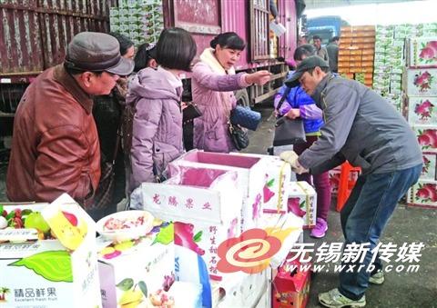 买水果的市民排队等成箱打包。