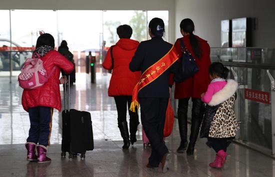 帮助带小孩的旅客提行李出站