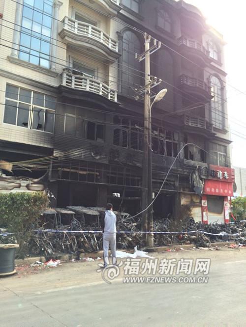 车行的两轮车都被烧得只剩下骨架了,事发楼房外墙也都被熏黑。