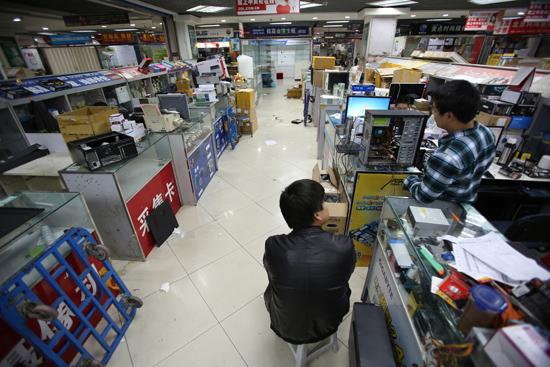 1月22日,北京中关村e世界电子市场一楼已经没有商铺,二至四层的店铺还在营业,有的已经陆续撤离,只有一两名顾客前来购买电子产品。CFP供图