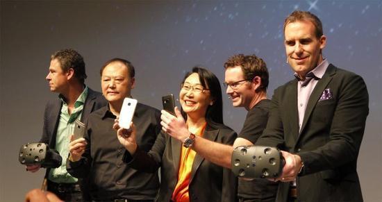 宏达电董事长王雪红(中)、HTC执行长周永明(左二)于巴塞罗那全球新机发表会上开心展示HTC One M9。