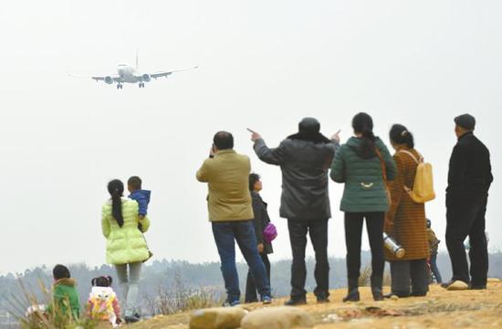 3月2日,二跑道旁市民打堆堆看飞机。