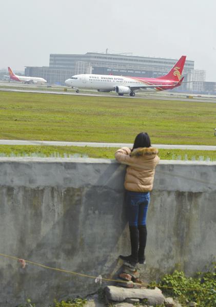 成都1号跑道外趴墙看飞机起飞的市民。