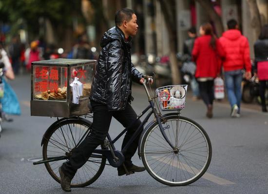 店铺的饼销量不多,梁乙彬每天都单手骑车沿街卖饼。
