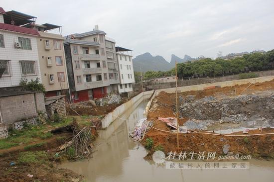倾斜的房屋旁是一个在建工地。