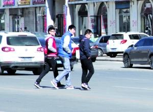 仨年轻人快速横穿,其中一人还低头看手机