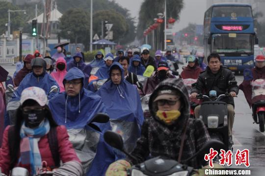 """图为10日,南宁街头着厚重御寒""""装备""""的市民。宋汉涛 摄"""