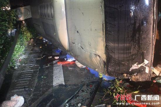 图为事故现场1名乘客被压在侧翻的大客车下面