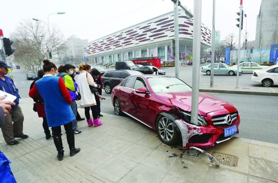 奔驰车冲上了约40厘米高的路阶,路阶上的一根信号灯杆不幸遭殃。