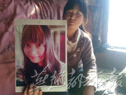小丽母亲拿着小丽生前照片