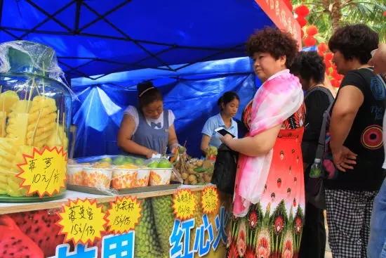 庙会现场,热带水果颇受青睐,图为游客排队买水果