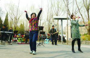 今天,通州玉桥中路的街边公园内,一名大妈乘鼓起舞。晨报记者 柴春霞