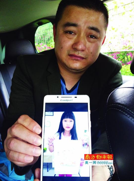 李先生从手机中翻出女儿的照片。南都记者 徐文阁 摄