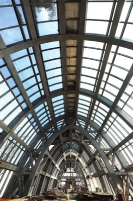 """在""""东方之门""""顶层,每一组玻璃之间都用很粗的拱顶钢结构连接,抛物线形的穹顶,显得空间十分开敞。"""