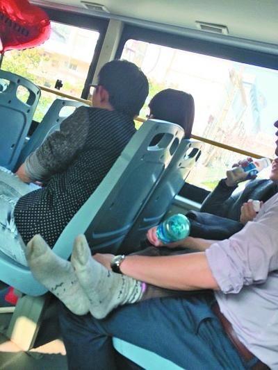 女子脱去鞋袜,双腿放在男子腿上。