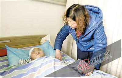 8日,新桥医院,母亲杨天平为莹莹按摩手臂。