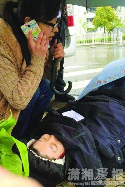 4月7日,中南大学升华学生公寓附近,秦丹丹用手机拨打电话,另一只手撑伞为晕倒女子挡雨。之后陆续有路人前来帮忙,直到救护车到来。