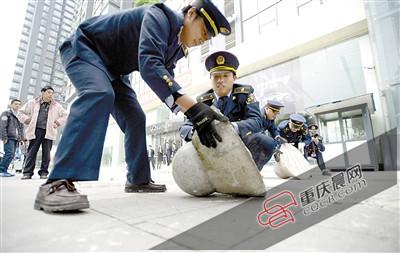 10日,渝北区市政综合执法支队龙塔大队的执法人员在紫荆路清除临街门面设置的人行道上用于占道停车的障碍物。