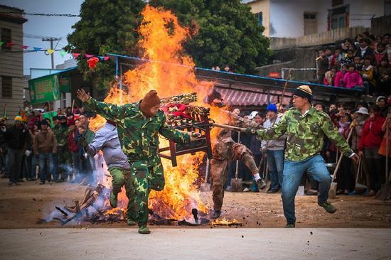 """漳浦佛昙每年都有抬""""开漳圣王""""跳火堆的习俗,是在祖祠前将木炭等点燃,顿时火苗冲天,人们抬着""""开漳圣王""""从燃烧的火堆上跳过。"""