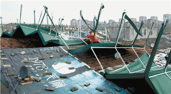 大风刮起半个篮球场大的钢棚,掀翻后砸上民房顶。