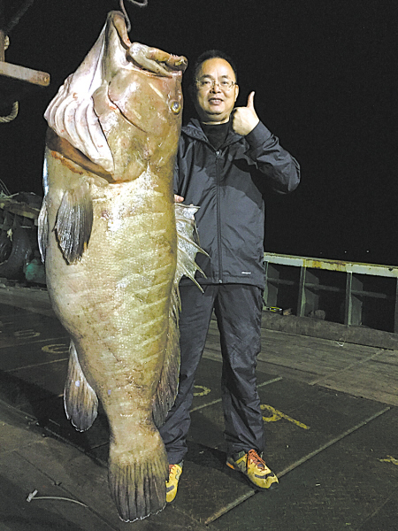 """图为胡祖岳和他钓到的""""东海第一石斑鱼""""。"""