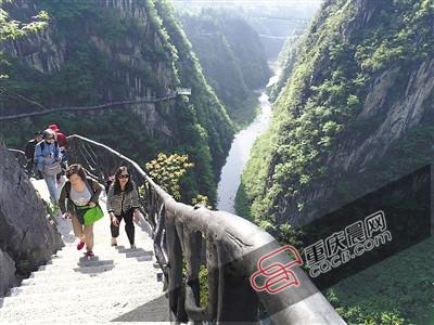 昨日,黔江城市大峡谷,游客正经过依山势而建的悬崖栈道,远处就是一期工程中的玻璃栈道。